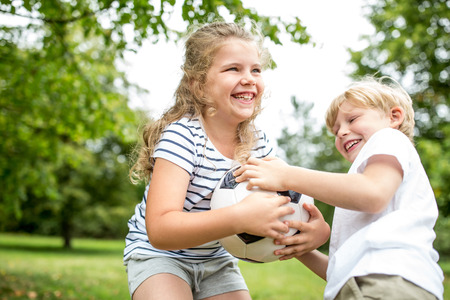 argue kid: Controversy between children and a ball during family soccer match Stock Photo
