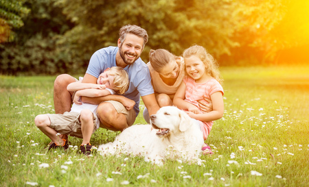 Happy family with children and dog in summer in the garden Archivio Fotografico