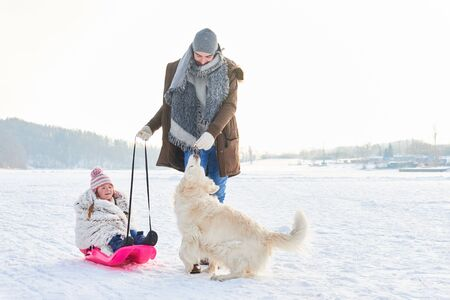 Father and daughter playing with dog in winter in the snow