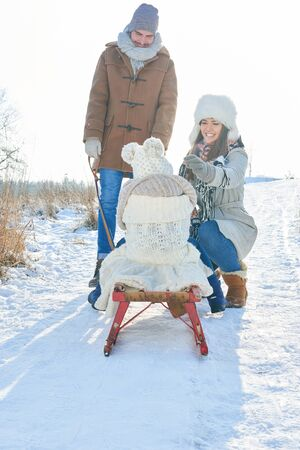 Parents playing with daughter on sled in winter on the snow Stock Photo