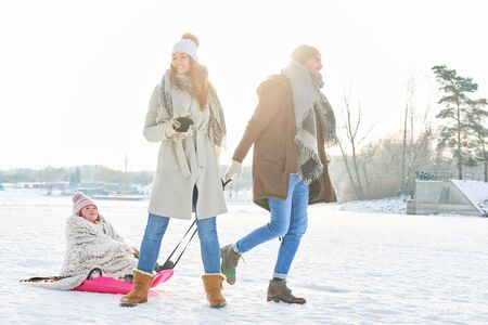 Family taking a winter walk in the nature with child on sled