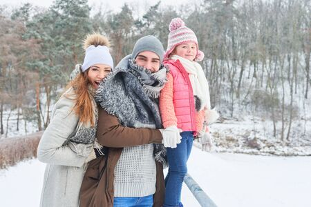Happy parents together with daughter in winter holiday trip