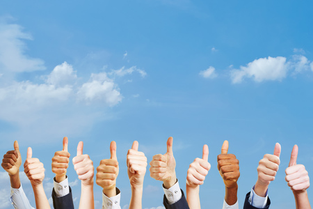 Many hands holding thumbs up as motivation at work concept Stock Photo
