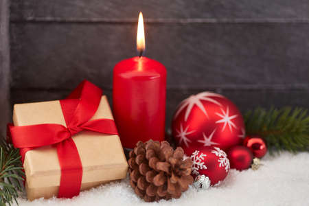 Christmas gift and red candle with wooden background Stock Photo