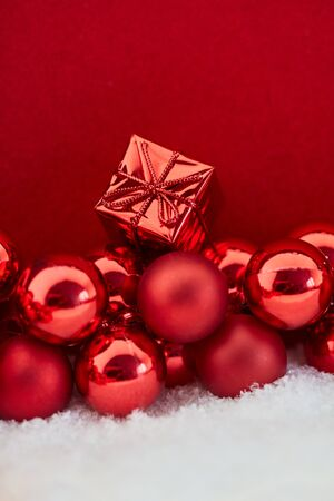 Small christmas present on red baubles as background