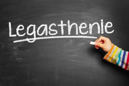 Kid schrijft Legasthenie (dyslexie) op schoolbord op school