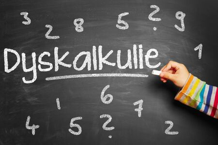 Kid writes Dyskalkulie (dyscalculia) on blackboard at school