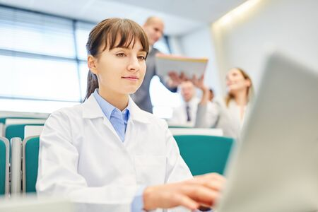 Young woman as medicine student with laptop learn in apprenticeship Stock Photo