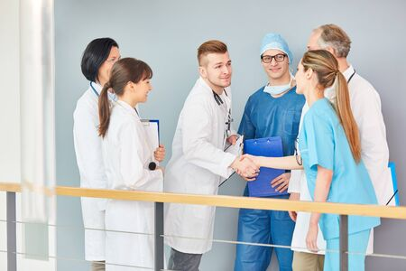 Young doctor in training shake hands with team of doctors