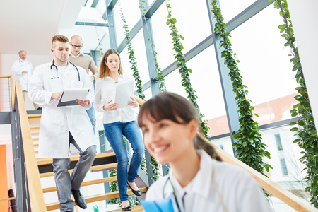 Doctors in medical apprenticeship walking down hospital stairs Banque d'images