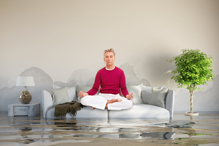 Relaxed man doing yoga after water damage on his sofa (3D Rendering) Stock Photo
