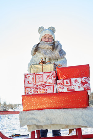 Gril standing behind christmas gifts on sled as winter surprise Lizenzfreie Bilder