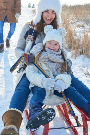 Mother and daughter playing with sled together and having fun Lizenzfreie Bilder