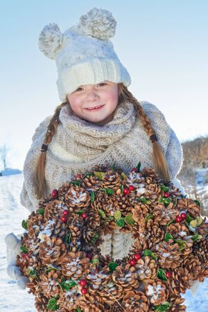 Girl holding advent wreath for christmas in winter
