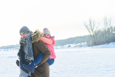 Father gives daughter piggyback ride in winter and have fun in the snowey nature Lizenzfreie Bilder