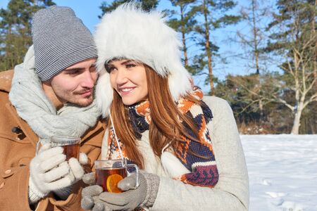 Couple in love during their winter vacation drinking hot tea