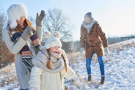 Parents and daughter as family have fun with snowball fight in winter Stock Photo