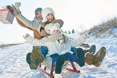 Family have fun with sled in winter and driving with christmas present Lizenzfreie Bilder
