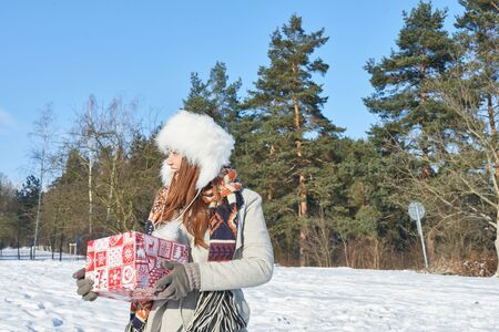 Young woman holding christmas gift and walking in winter