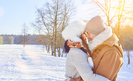 Couple in love embrace in winter in the snow kissing