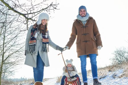 Happy parents pull child on sled on the snow