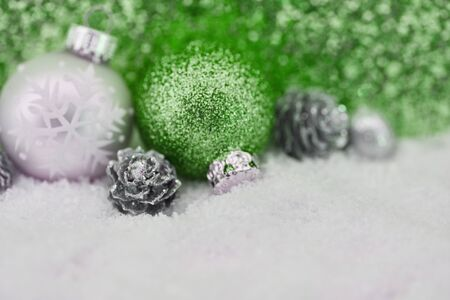 Green christmas decoration as background with bauble and pir cone
