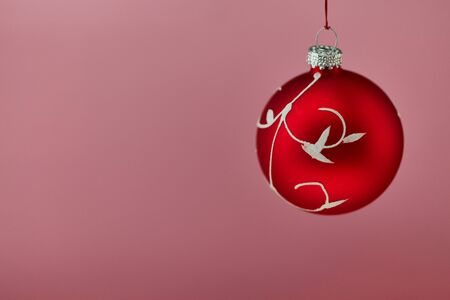 Big red christmas bauble on pink background for card