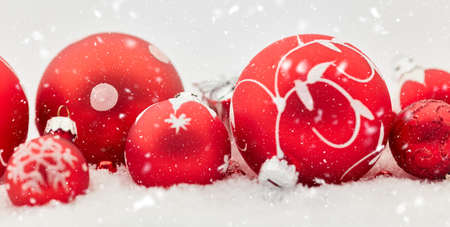 Snow and red christmas baubles as decoration for background