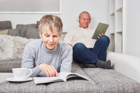 Woman as senior with a book on the couch for relaxation Banque d'images