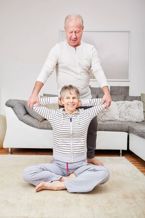Seniors make fitness exercise and help each other stretching