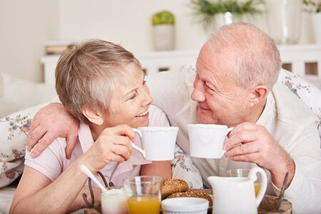 Seniors in love have romantic breakfast in bed together  Banque d'images