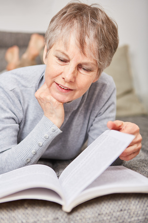 Woman as senior reading a book with curiosity