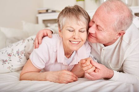 Senior man kissing wife in bed with love Banque d'images