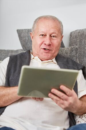 Senior man holding tablet computer at home on the couch