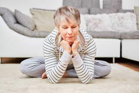 Senior woman makes meditation exercise for relaxation in wellnes Lizenzfreie Bilder