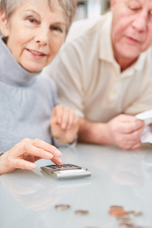 Senior woman using calculator with husband for home accounting