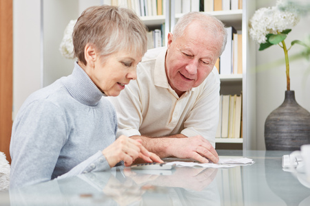 Senior couple calculating with calculator the finance costs