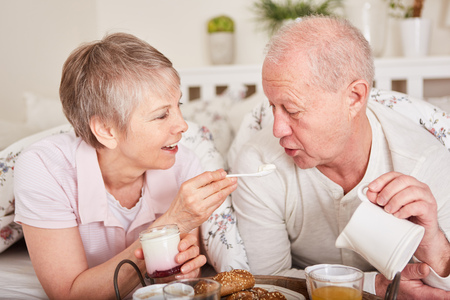 Seniors have breakfast in bed as a happy couple