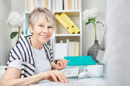 Woman as senior business citizen working at her place of work