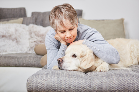 Lonely woman cuddles with dog pet on the couch