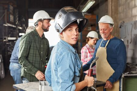 Young woman in apprenticeship lesson as blue collar worker Banque d'images