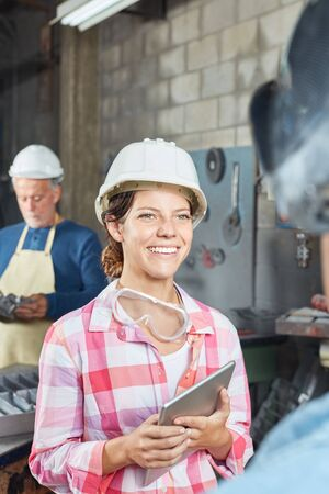 Young woman as metalworker apprentice with laptop in metallurgy factory Stock Photo