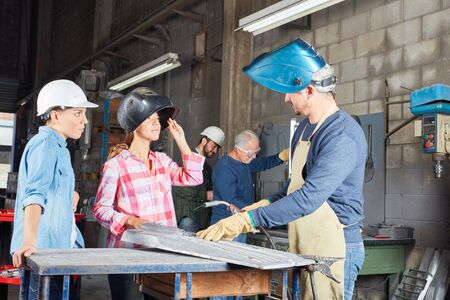 Women in welding apprenticeship lesson in metallurgy workshop Lizenzfreie Bilder