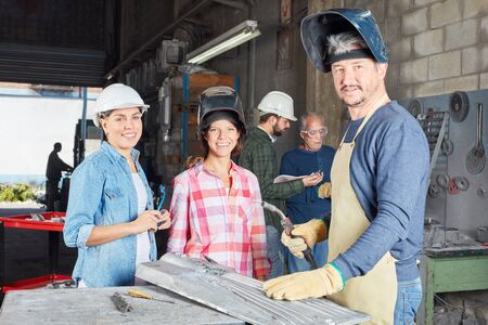 Man as welder instructor with two trainee women in metallurgy lesson