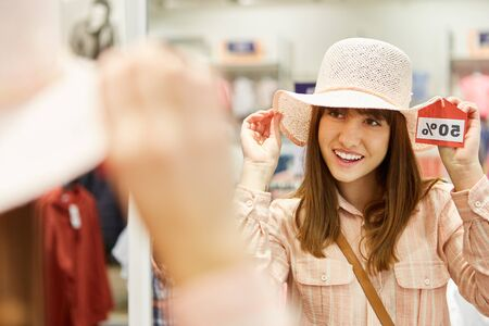 Young woman shopping tries a hat on offer in fashion shop