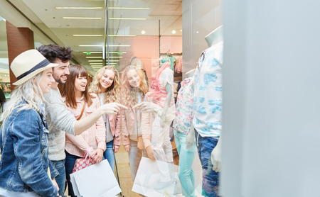 Group of teenagers is having fun shopping in front of a shop window