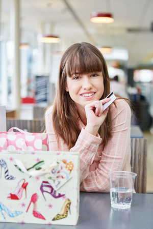Young woman with credit card pauses while shopping at mall Lizenzfreie Bilder