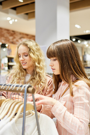 Two young women shopping for clothes in a fashion store Lizenzfreie Bilder