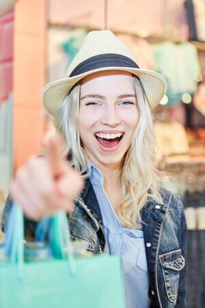 Young blond woman laughs while shopping in shopping mall