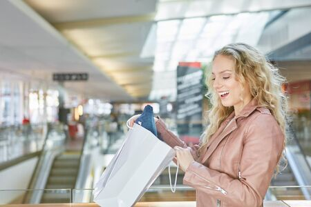 Young blond woman looks surprised into a grocery bag after shopping